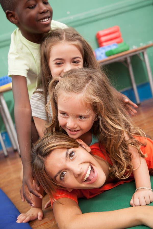 Leraar met van haar studenten die op de vloer spelen stock foto's