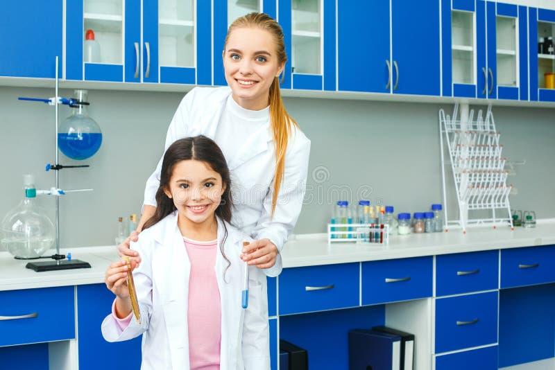 Leraar met weinig kind in de holdings test-buis van het schoollaboratorium stock foto