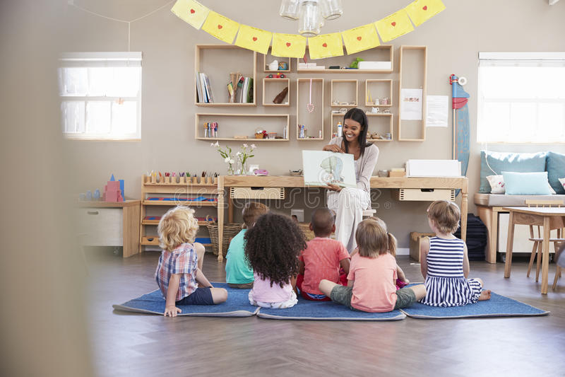 Leraar At Montessori School die aan Kinderen in Verhaaltijd lezen stock afbeelding