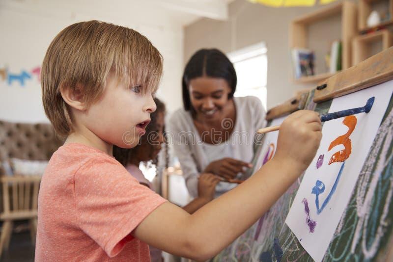 Leraar At Montessori School die Kinderen in Art Class helpen stock afbeeldingen