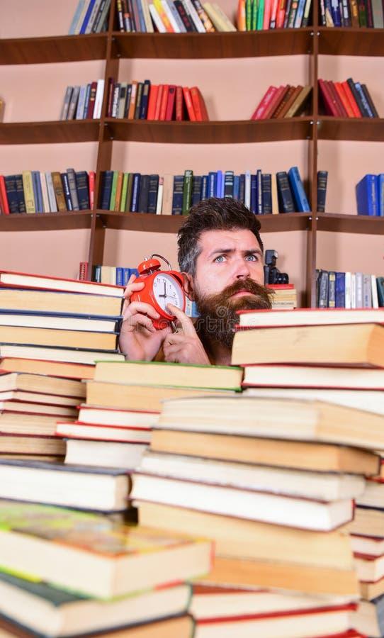 Leraar of student die met baard in bibliotheek bestuderen Mens, wetenschapper die uit stapels van boeken met wekker gluren Mens  royalty-vrije stock foto's