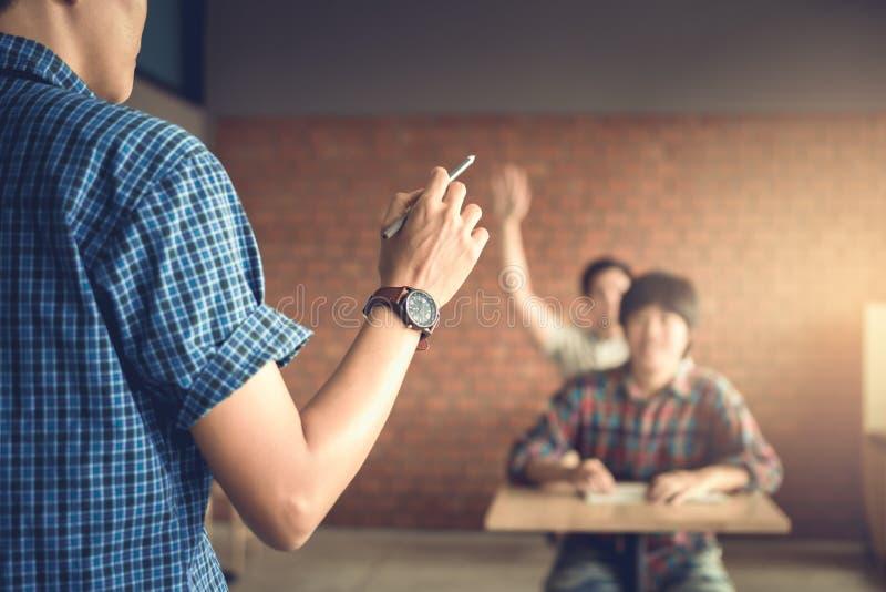 Leraar vragen stellen en student die handen opheffen aan het antwoorden royalty-vrije stock foto