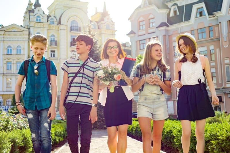 Leraars` s Dag, openluchtportret van gelukkige midden oude vrouwelijke middelbare schoolleraar met boeket van bloemen en groepsst royalty-vrije stock afbeeldingen
