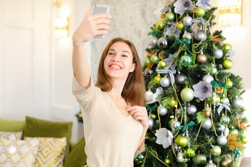 Leraarsmeisje die selfies dichtbij Nieuwjaarboom nemen die smartphone gebruiken stock fotografie