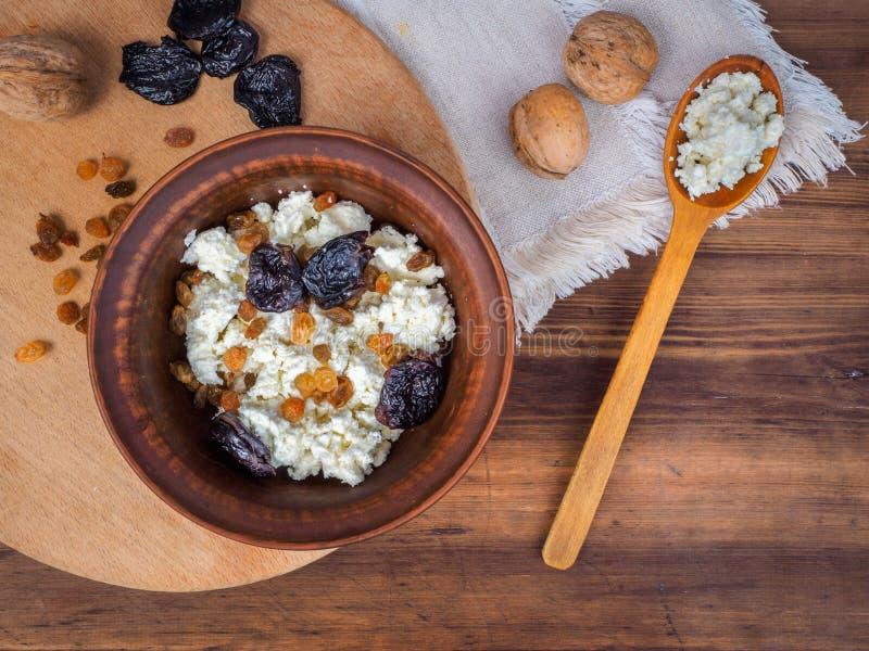 Lerabunke med keso, russin och torkade aprikors bredvid de träskeden och valnötterna Mejeriproduktstuga fotografering för bildbyråer