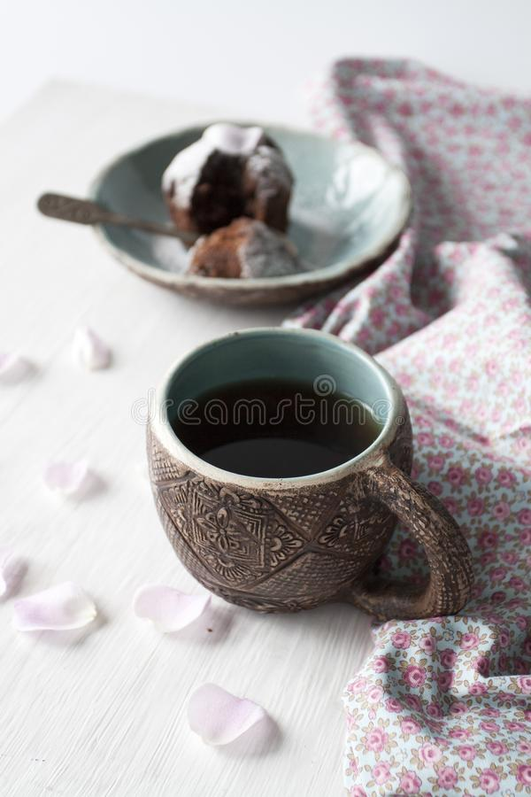 Lerakopp med blått i mitt och en platta med en muffin royaltyfri bild