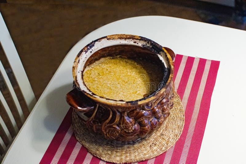 Lerakrukan med bakat mjölkar Soured hemlagat mjölkar i en lerabunke Melted mjölkar från den ryska ugnen Lantlig stil arkivfoto
