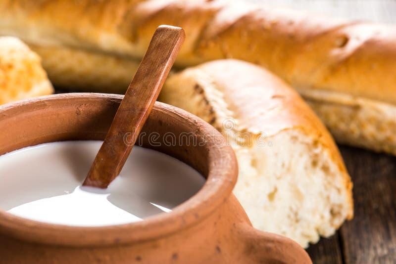 Lerakrukan med lantligt mjölkar och den varma bagetten royaltyfria foton
