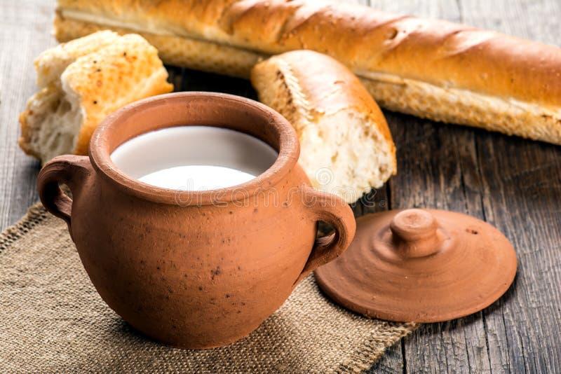 Lerakrukan med lantligt mjölkar och den varma bagetten royaltyfria bilder