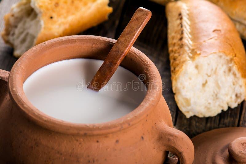 Lerakrukan med lantligt mjölkar och den varma bagetten arkivbild