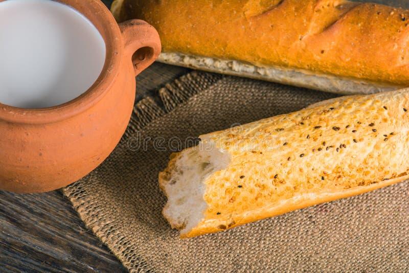 Lerakrukan med lantligt mjölkar och den varma bagetten arkivfoton