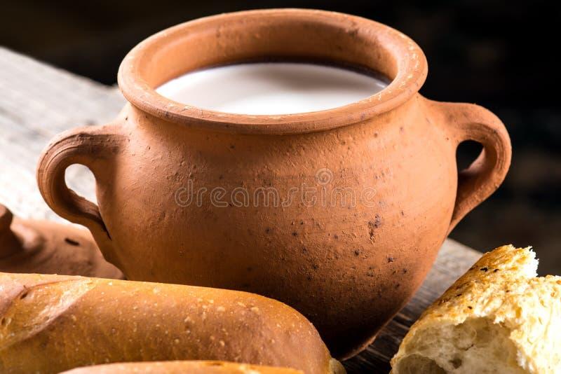Lerakrukan med lantligt mjölkar och den varma bagetten fotografering för bildbyråer