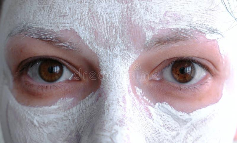 Leramaskering på en kvinnaframsida Närbildbruntögon royaltyfria bilder