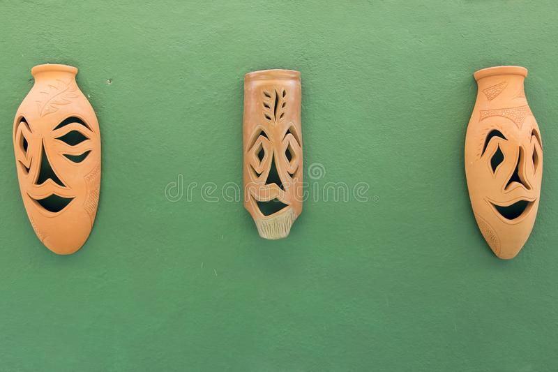 Leramaskeringar hänger på en grön vägg royaltyfri foto