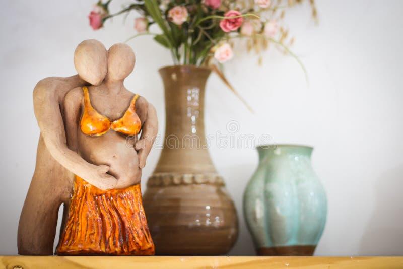 Leraskulptur av pergnant par royaltyfri bild