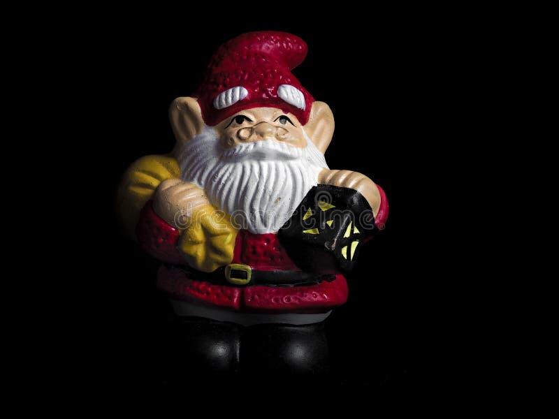 Lerastatyetten av Santa Claus isolerade på svart arkivfoton