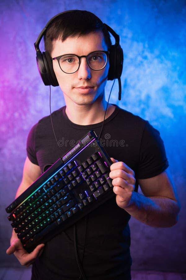 Lerdo do computador com o teclado sobre o rosa colorido e a parede leve de néon azul fotografia de stock