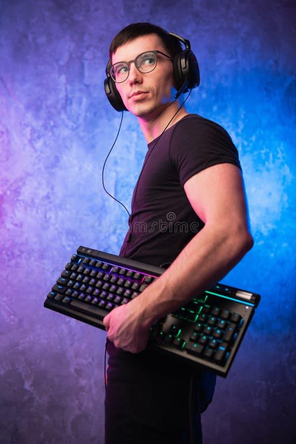 Lerdo do computador com o teclado sobre o rosa colorido e a parede leve de néon azul foto de stock royalty free