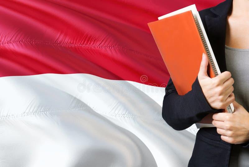 Lerend Indonesisch taalconcept Jonge vrouw die zich met de vlag van Indonesië op de achtergrond bevindt De boeken van de leraarsh stock afbeeldingen