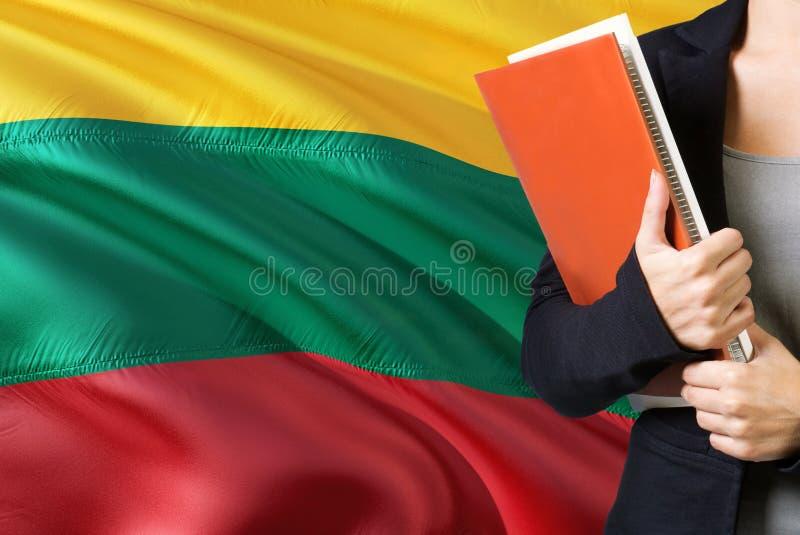 Lerend Litouws taalconcept Jonge vrouw die zich met de vlag van Litouwen op de achtergrond bevinden De boeken van de leraarsholdi royalty-vrije stock afbeelding