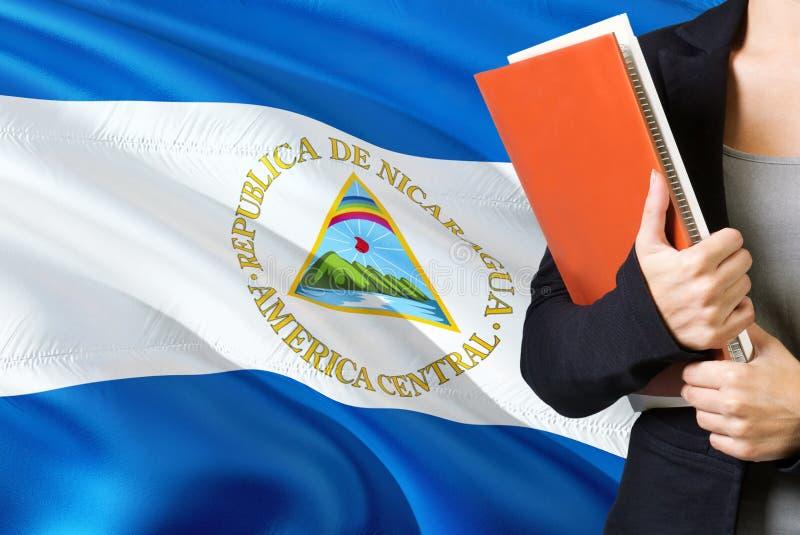 Lerend Nicaraguan taalconcept Jonge vrouw die zich met de vlag van Nicaragua op de achtergrond bevinden De boeken van de leraarsh stock foto's