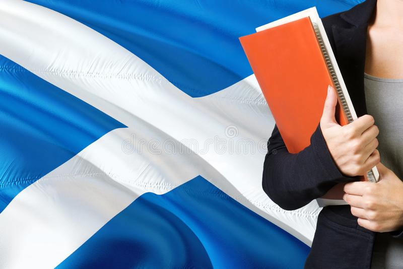 Lerend Schots taalconcept Jonge vrouw die zich met de vlag van Schotland op de achtergrond bevindt De boeken van de leraarsholdin stock afbeeldingen