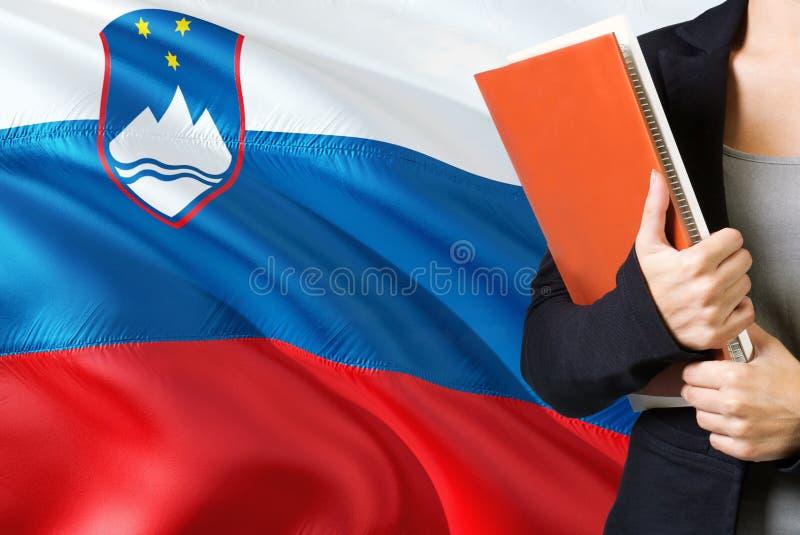 Lerend Sloveens taalconcept Jonge vrouw die zich met de vlag van Slovenië op de achtergrond bevinden De boeken van de leraarshold royalty-vrije stock fotografie