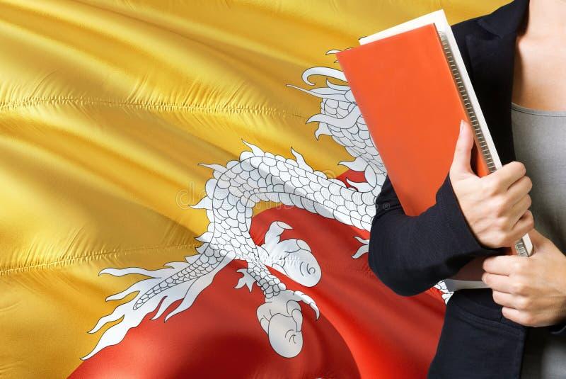 Lerend taalconcept Uit Bhutan Jonge vrouw die zich met de Bhutan vlag op de achtergrond bevinden De boeken van de leraarsholding, stock afbeelding