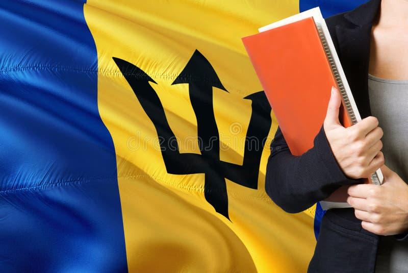 Lerend taalconcept Van Barbados Jonge vrouw die zich met de vlag van Barbados op de achtergrond bevinden De boeken van de leraars royalty-vrije stock fotografie
