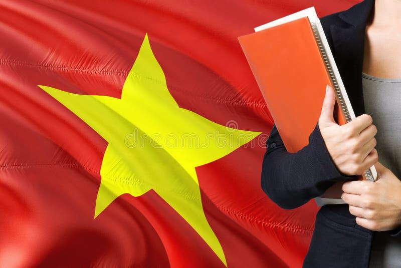 Lerend Vietnamees taalconcept Jonge vrouw die zich met de vlag van Vietnam op de achtergrond bevinden De boeken van de leraarshol royalty-vrije stock foto