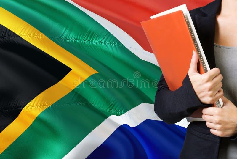 Lerend Zuidafrikaans taalconcept Jonge vrouw die zich met de vlag van Zuid-Afrika op de achtergrond bevinden De boeken van de ler stock foto