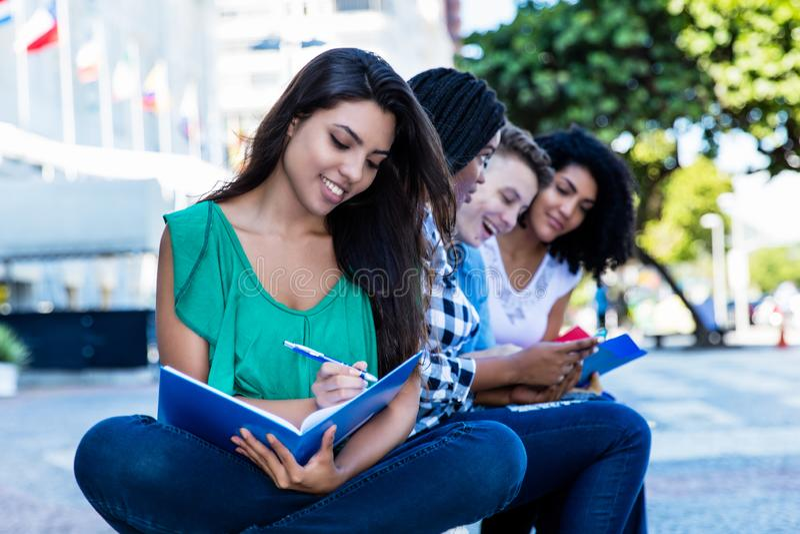 Lerende Latijns-Amerikaanse vrouwelijke student met groep internationale studenten openlucht in de zomer in de stad stock afbeeldingen