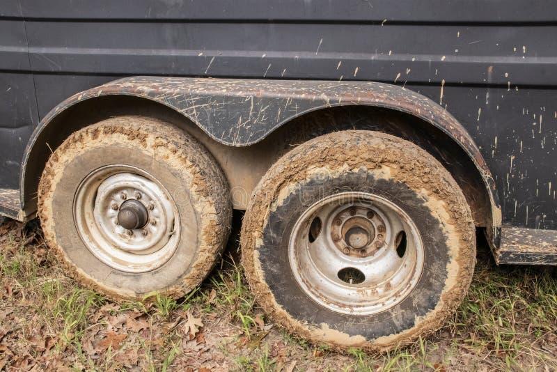Leriga gummihjul av nötkreatur eller hästsläp som sitter på gräs med gyttja som plaskas upp sida arkivbild