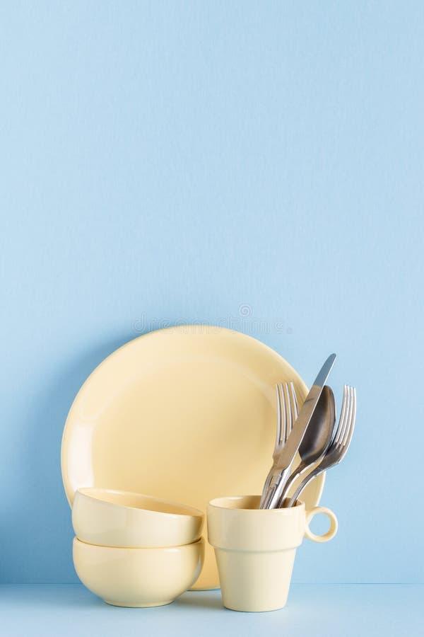 Lerkärl och bestick på en blå pastellfärgad bakgrund arkivbild