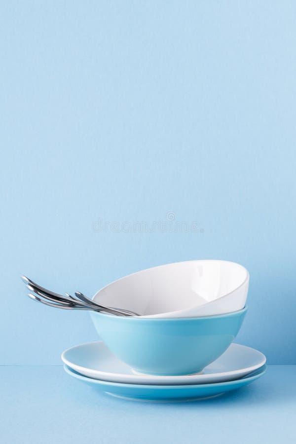 Lerkärl och bestick på en blå pastellfärgad bakgrund royaltyfria foton