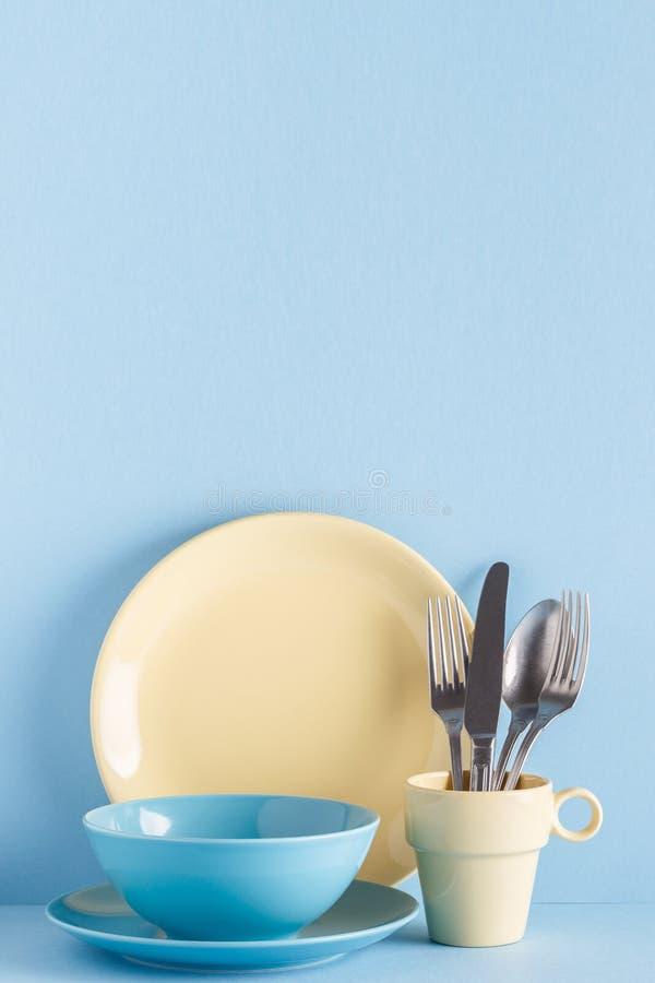 Lerkärl och bestick på en blå pastellfärgad bakgrund arkivbilder