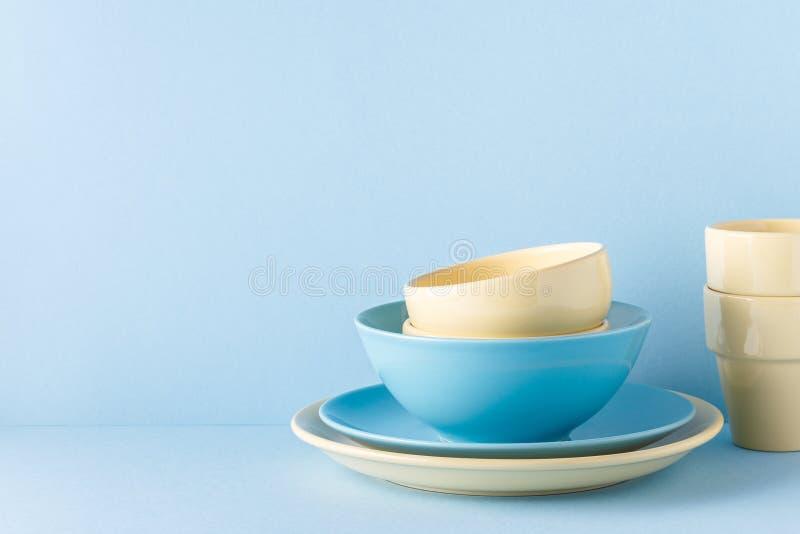 Lerkärl och bestick på en blå pastellfärgad bakgrund royaltyfri foto
