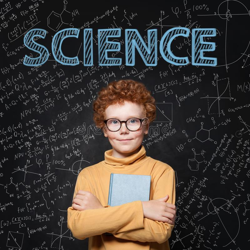 Lern Science. Clever student child on blackboard background with maths formulas.  royalty free stock photography