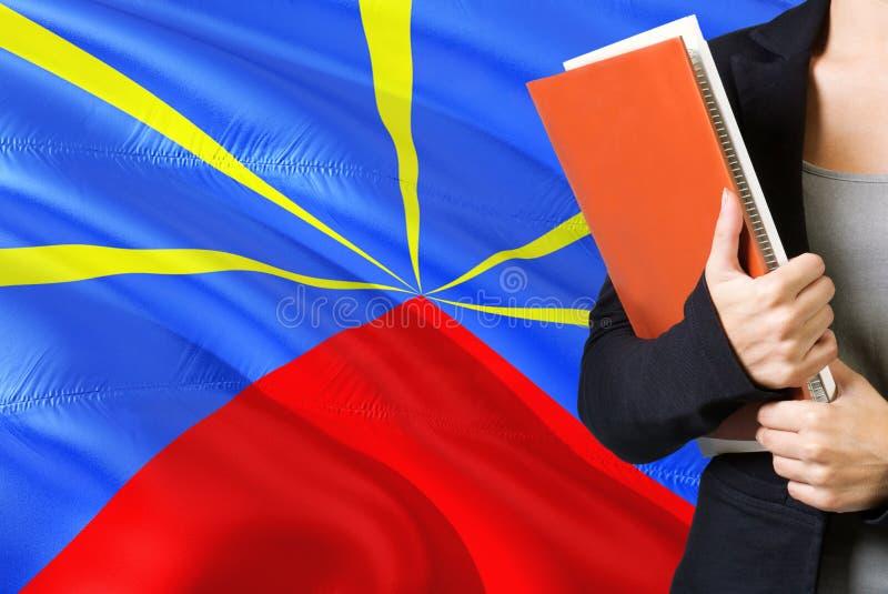 Lernen des franz?sische Sprachkonzeptes Stellung der jungen Frau mit der Réunions-Flagge im Hintergrund Lehrer, der Bücher, Orang lizenzfreie stockfotografie