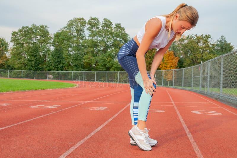 Lesão de joelho do esporte A mulher tem a dor no joelho após a corrida fora foto de stock royalty free