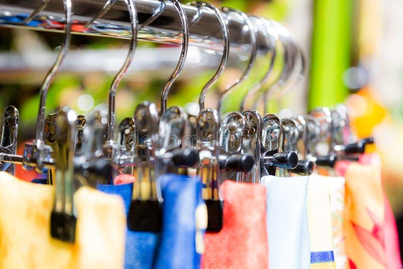 Les écharpes en soie sur des cintres dans la boutique au détail font des emplettes photographie stock