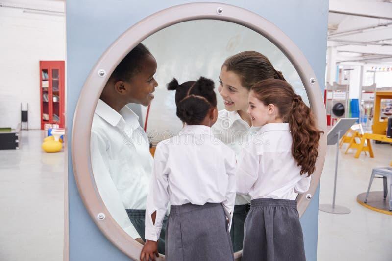 Les écolières regardant dans un miroir d'agrandissement la science centrent photographie stock
