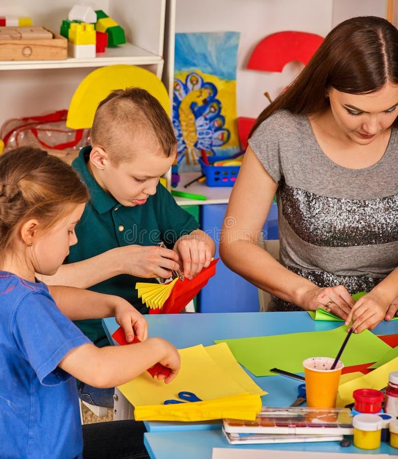 Les écoliers avec des ciseaux dans les enfants remet le papier de coupe image stock