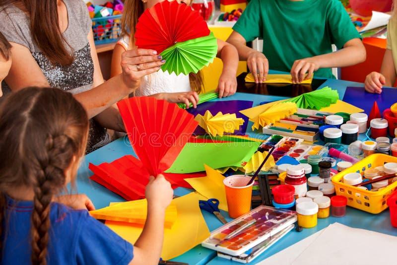 Les écoliers avec des ciseaux dans les enfants remet le papier de coupe photo stock