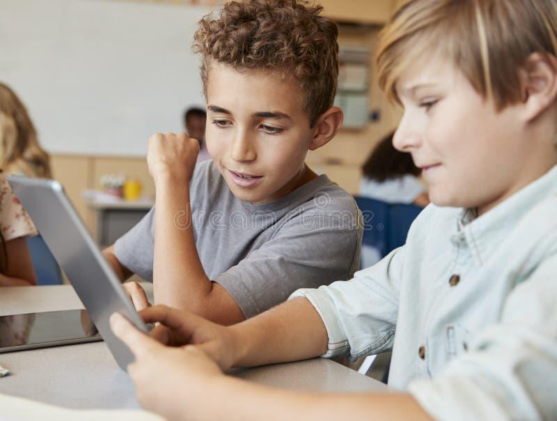 Les écoliers collaborant avec la tablette, se ferment  photographie stock