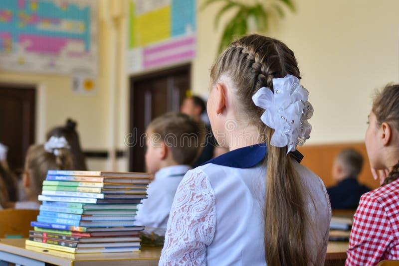Les écoliers d'enfants s'asseyent à leurs bureaux dans la salle de classe de l'école, le début de l'année scolaire, le 1er septem image stock