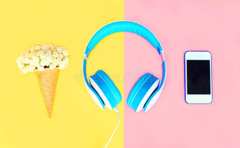 Les écouteurs avec le cornet de crème glacée fleurit le smartphone blanc au-dessus du rose jaune coloré photos stock