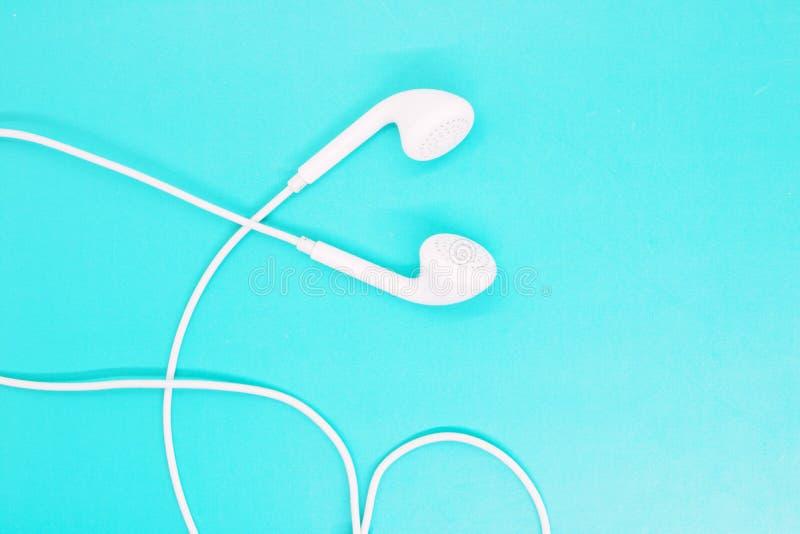 Les écouteurs blancs se ferment sur un fond de turquoise, écouteurs pour écouter la musique, instruments modernes, accessoires de images stock