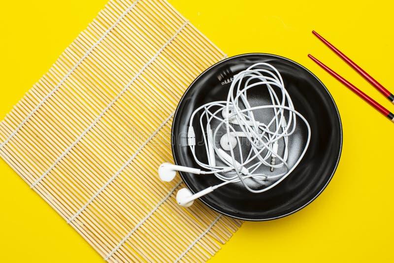 Les écouteurs dans un plat sur un tapis en bambou et un fond jaune lumineux, sont après des baguettes Concept de goût musical photo stock
