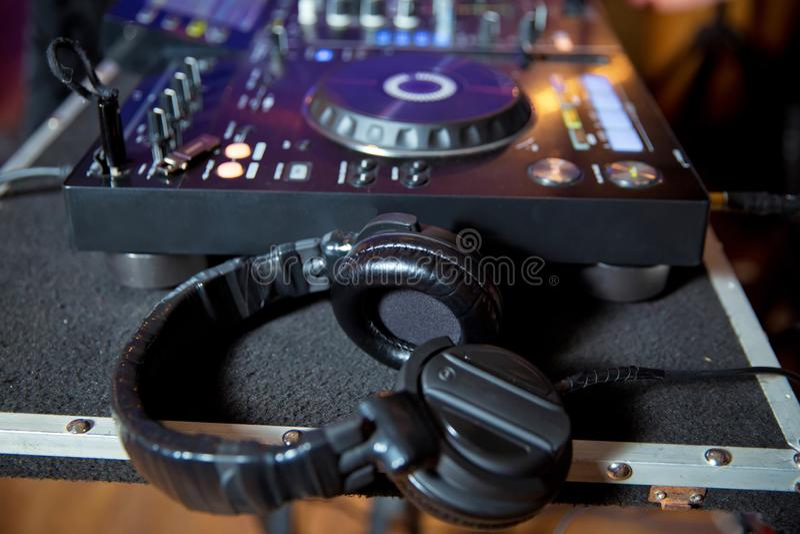 Les écouteurs professionnels sur le DJ embarquent dans la boîte de nuit Écouteurs sur le conseil du DJ dans la boîte de nuit photo libre de droits